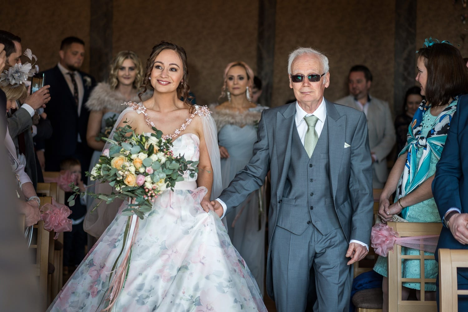 Bride walking down aisle with father at King Arthur Hotel in South Wales
