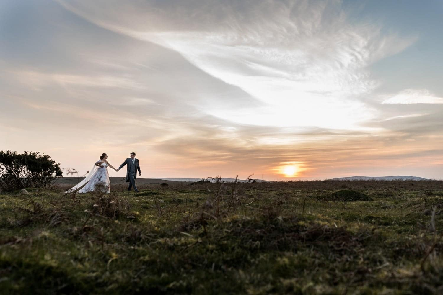 Bride and groom at the King Arthur Stone in Gower, South Wales on their wedding day