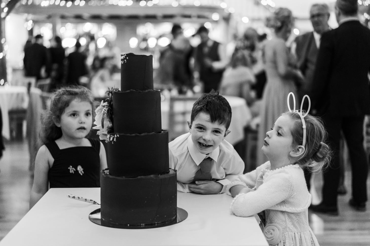 Children looking at the wedding cake at the King Arthur Hotel, Gower, South Wales
