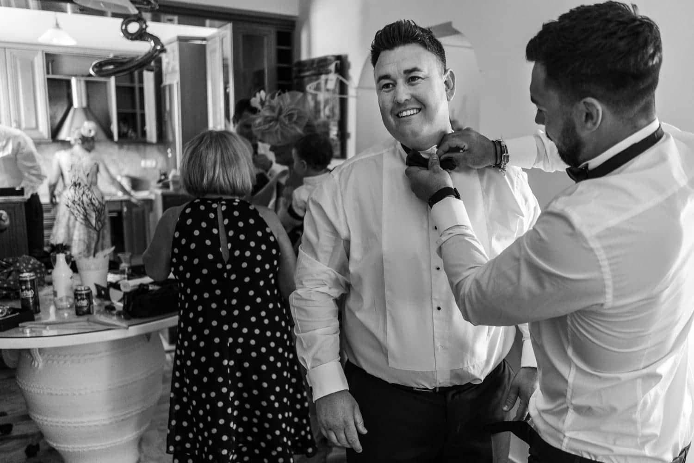 Santorini Wedding Photography, groom having tie put on