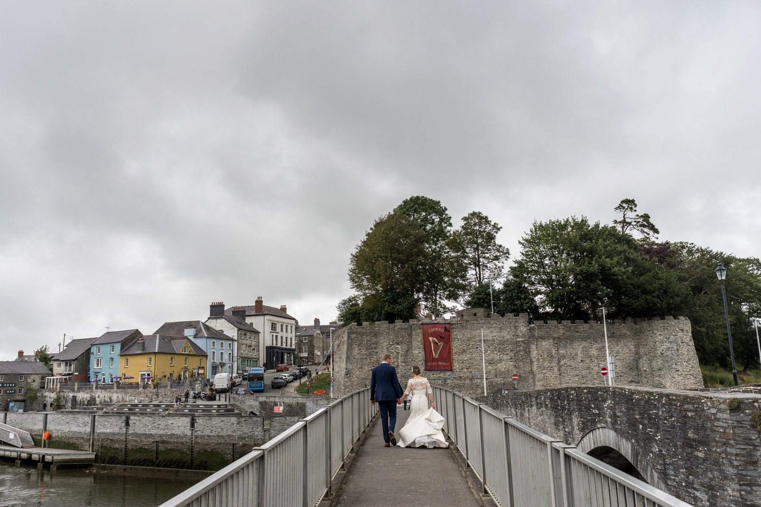 Bride and groom crossing River Teifi at Cardigan Castle