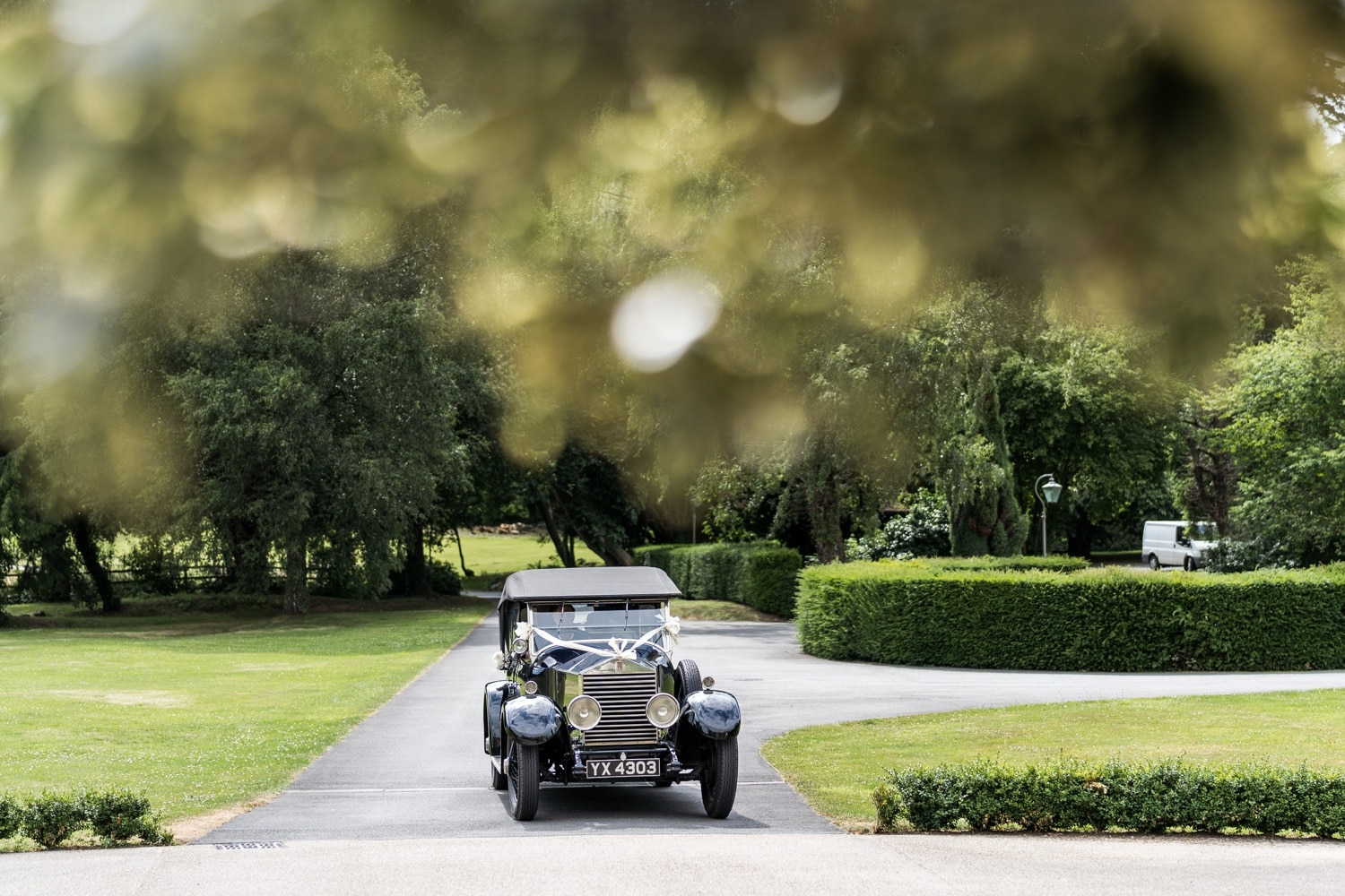 Vintage wedding car arrives at Llangoed Hall in Wales