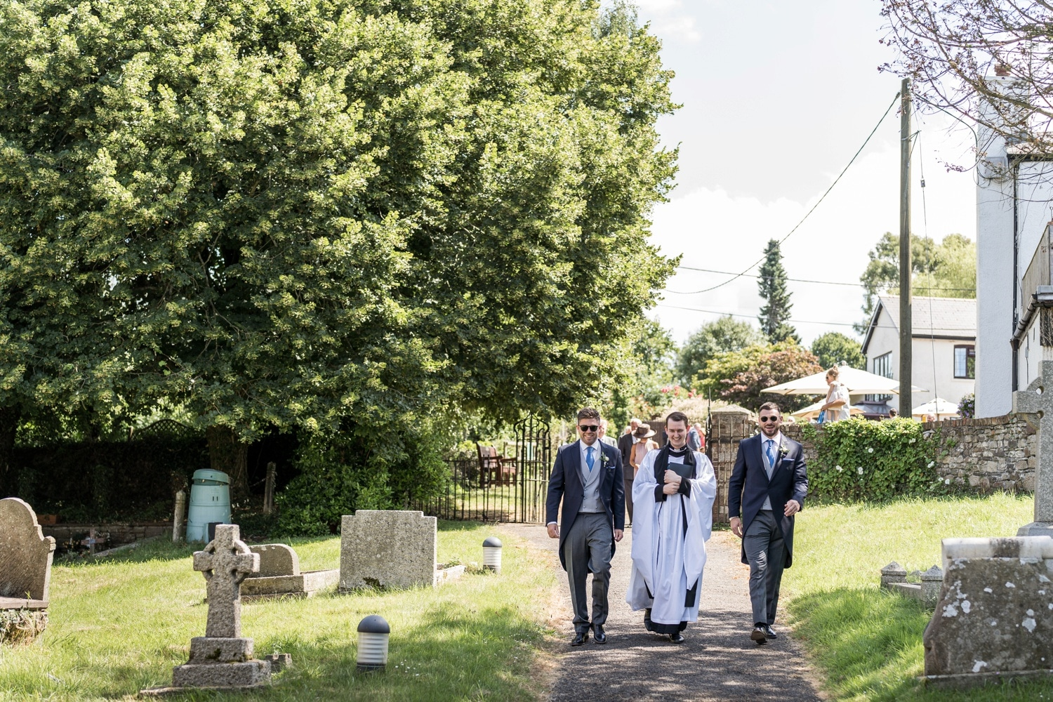 Groom with best man and vicar walks to church for wedding