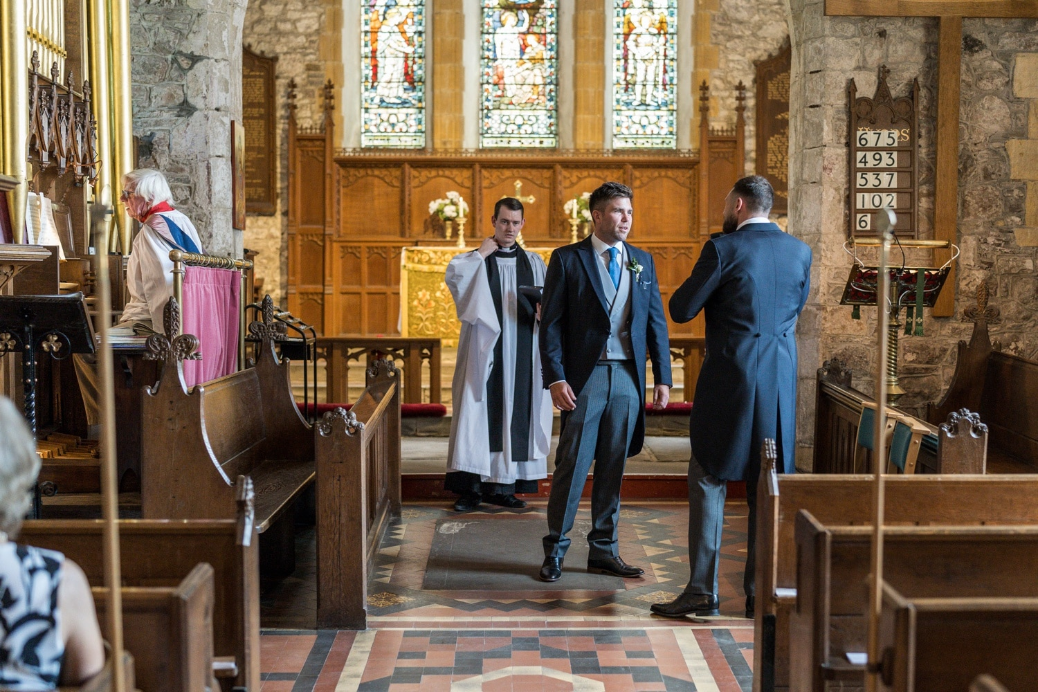 Groom with best man and vicar wait at church alter