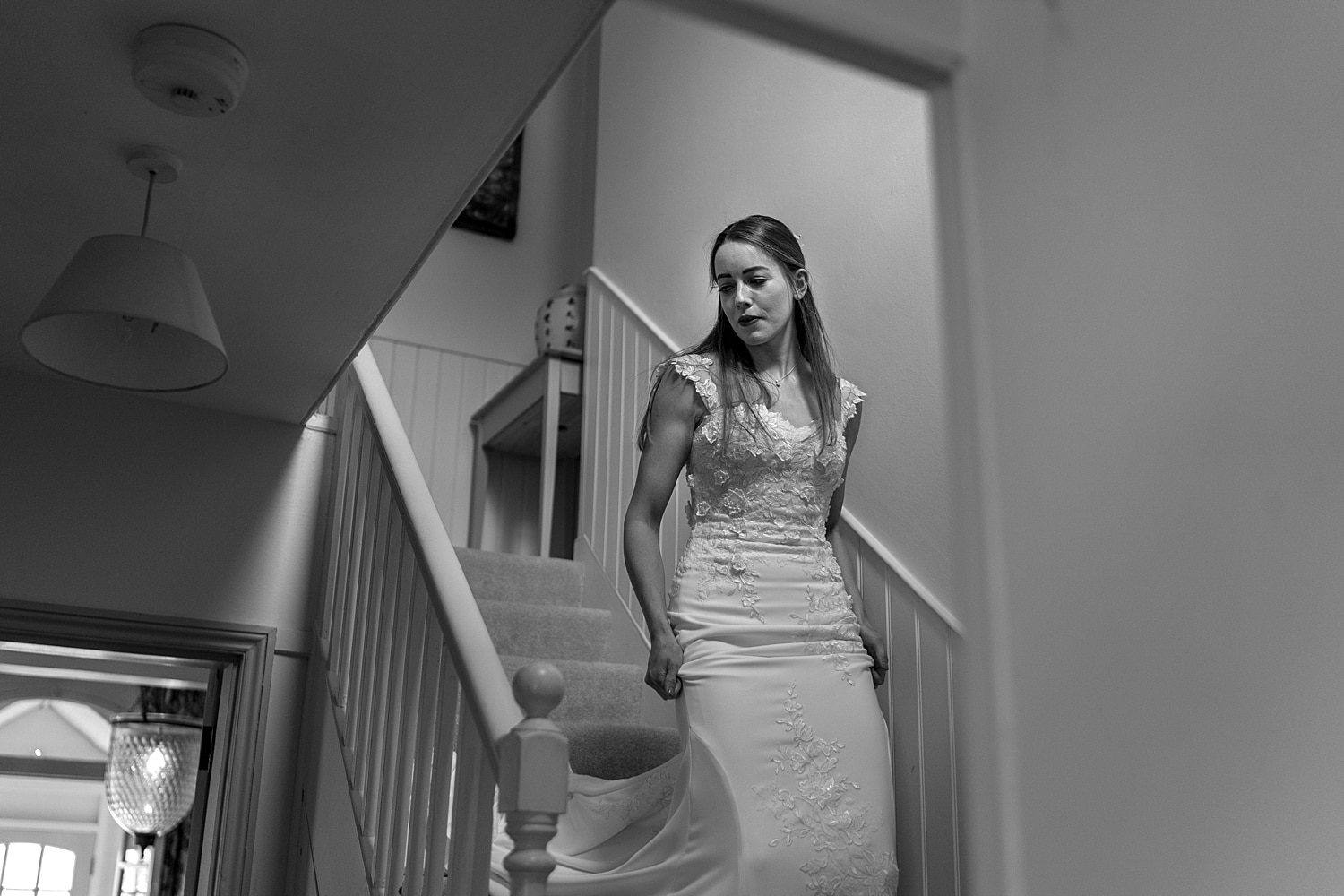 Bride descending stairs Groom getting ready at Euridge Orangery
