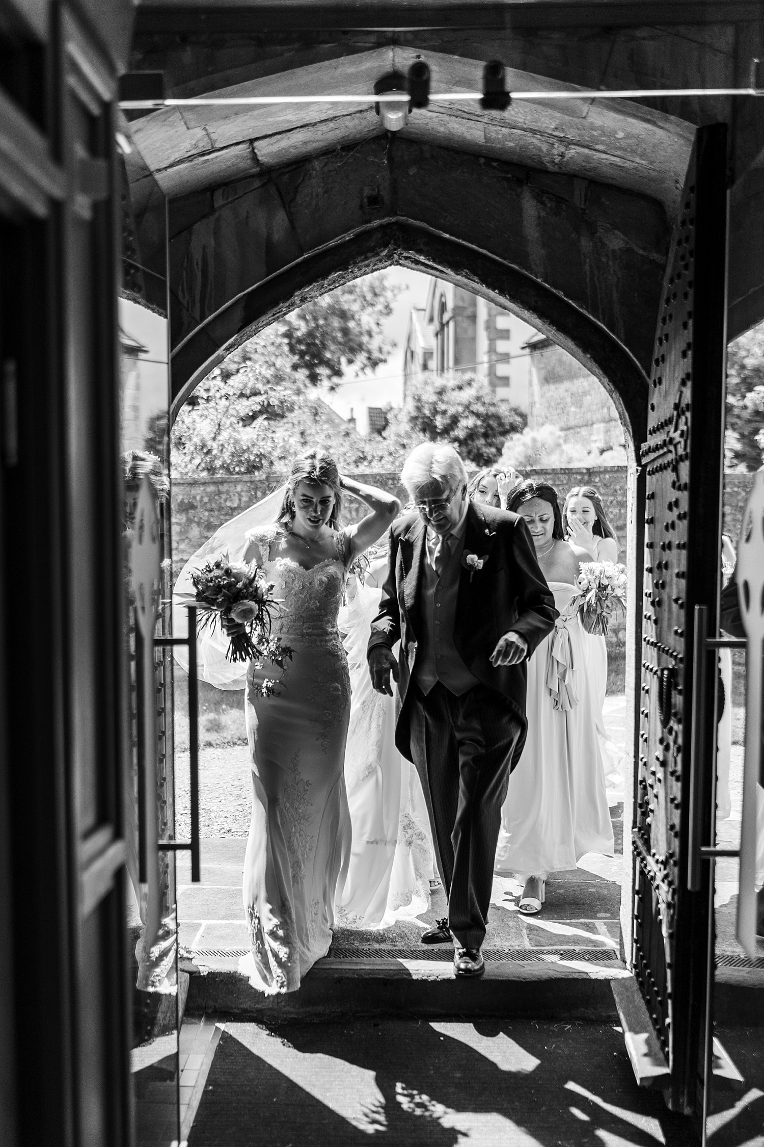 Bride walking through church door with father