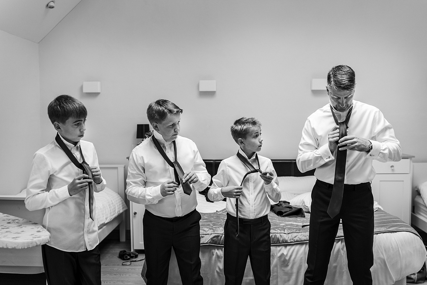 Page boys putting on ties