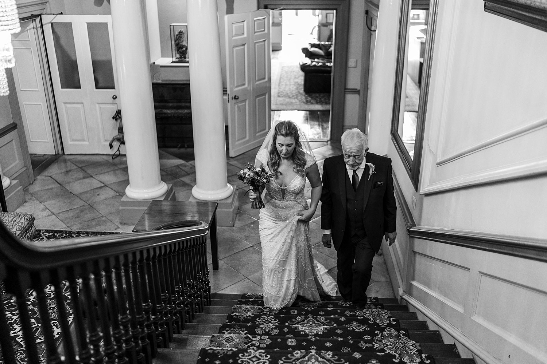 Bride adn father walking up stairs at Nanteos