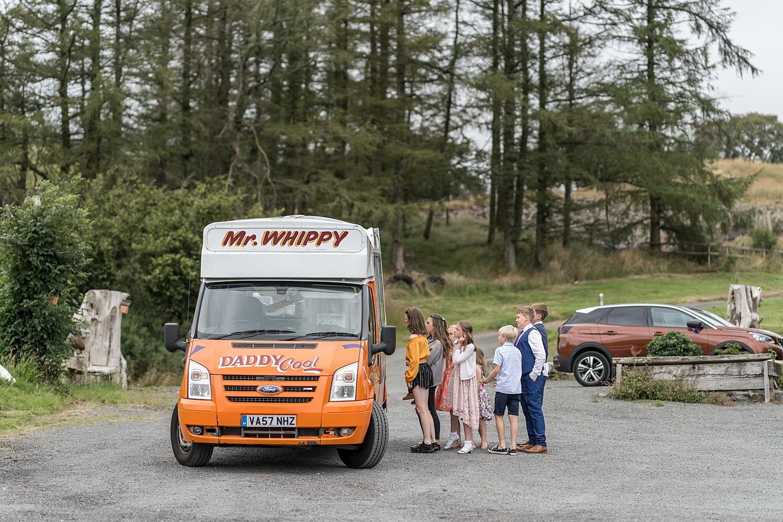 Children queueing for ice cream van at wedding reception