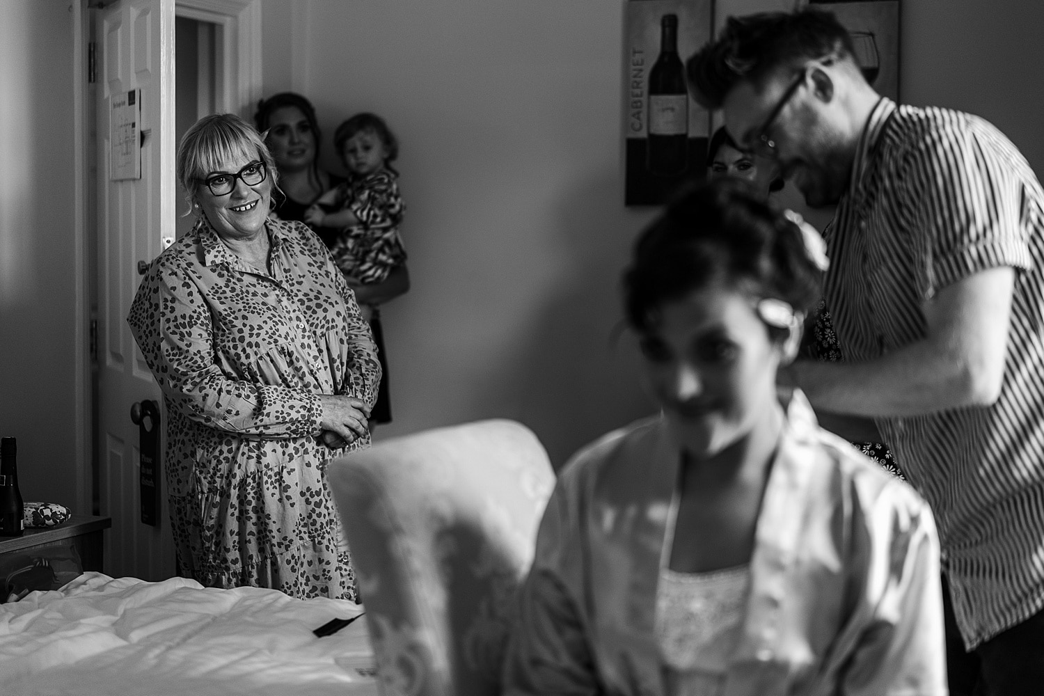 Mother looking onto bride as she gets ready for wedding