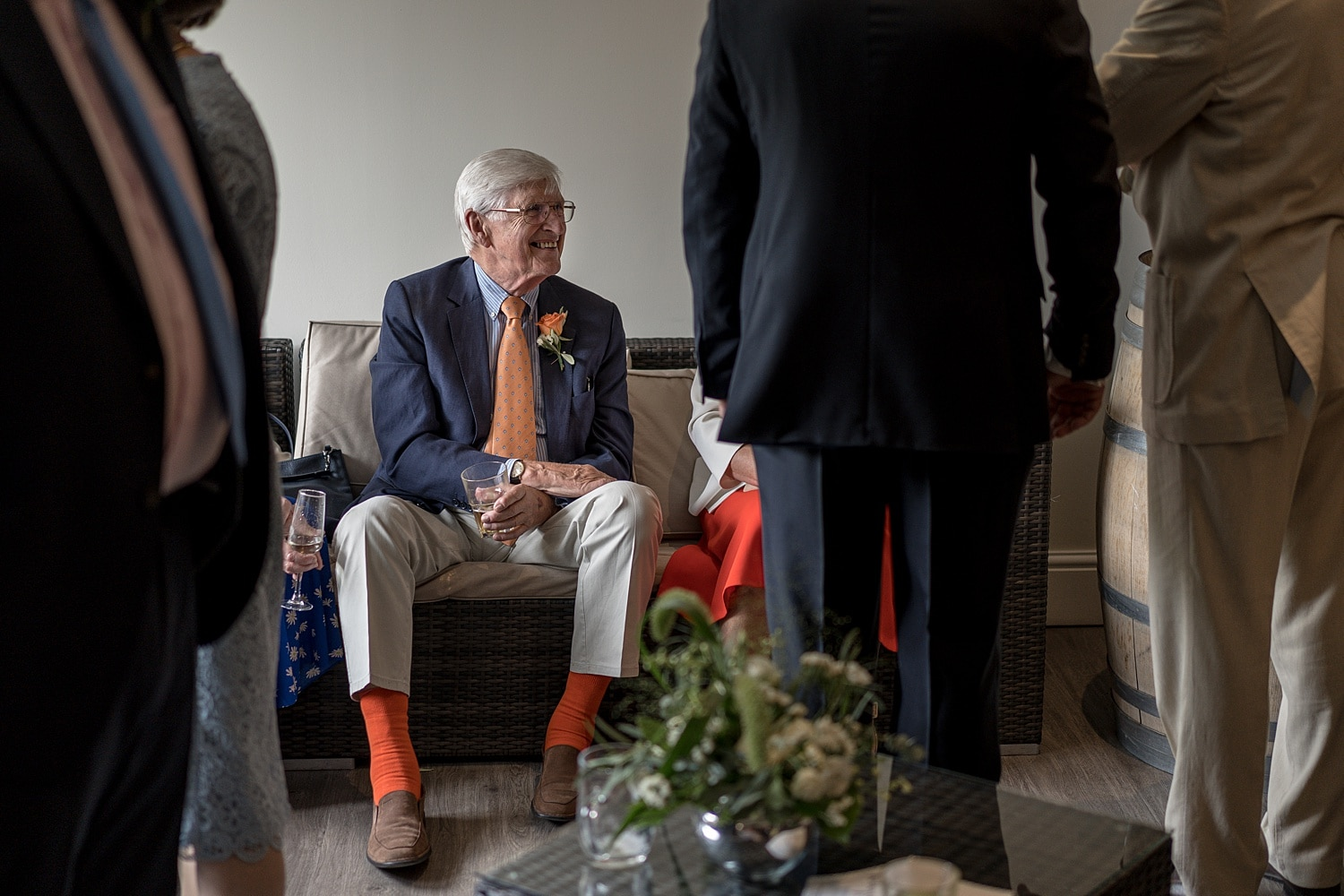 Wedding guest sitting down with orange socks