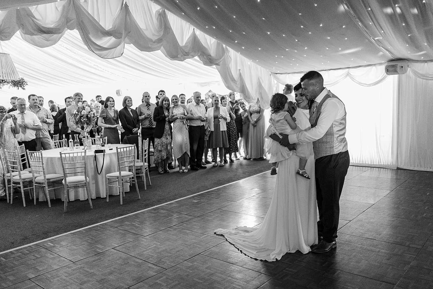 Bride and groom perform first dance with child