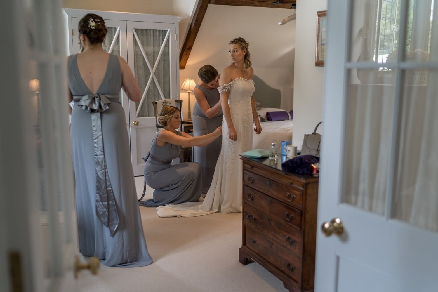 Bridemaids putting dress on the bride