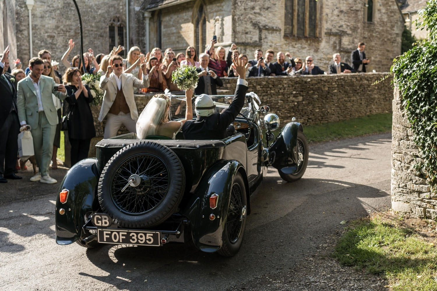 Groom drives his bride away in vintage car