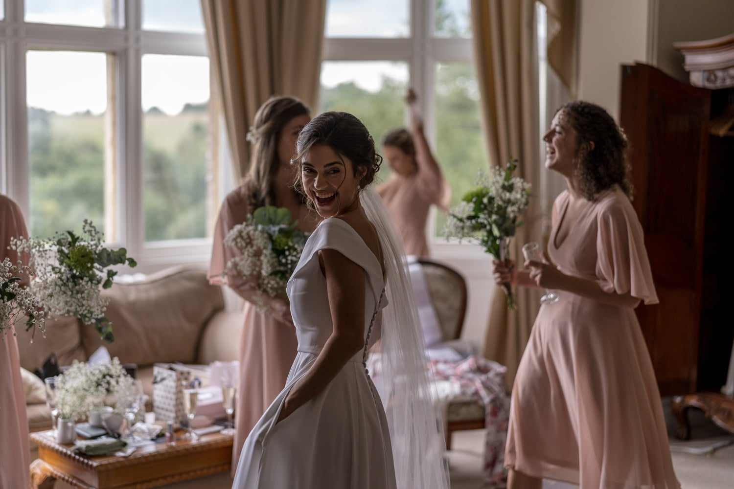 Bride laughing at Orchardleigh House, Somerset
