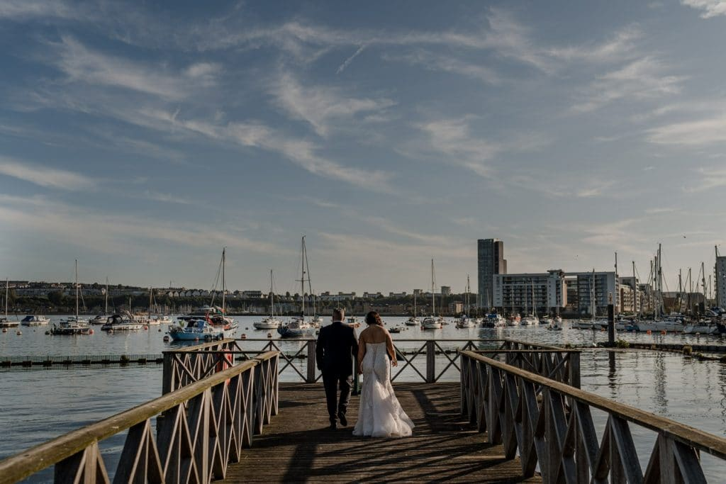 Bride and groom walking on jetty at Cardiff Bay