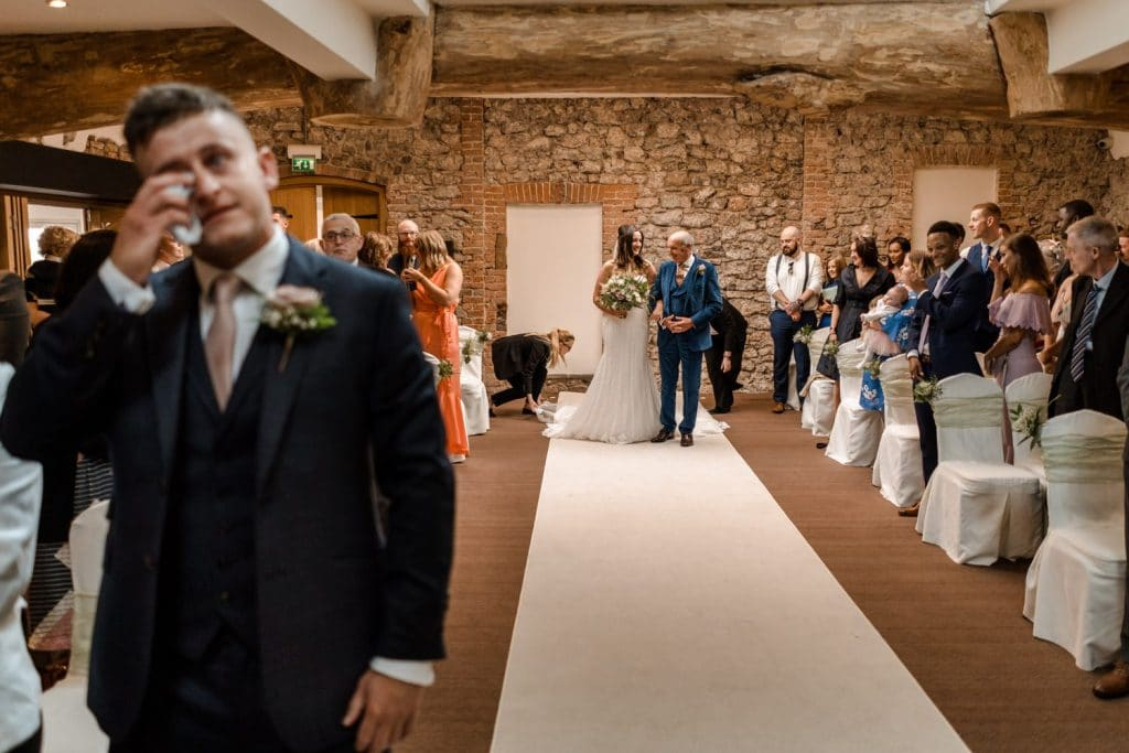 Groom crying as bride walks up aisle