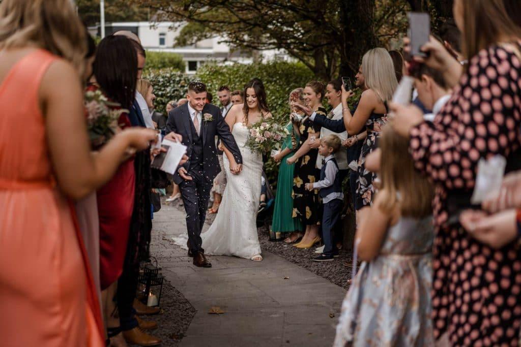 Bride and groom in confetti shower