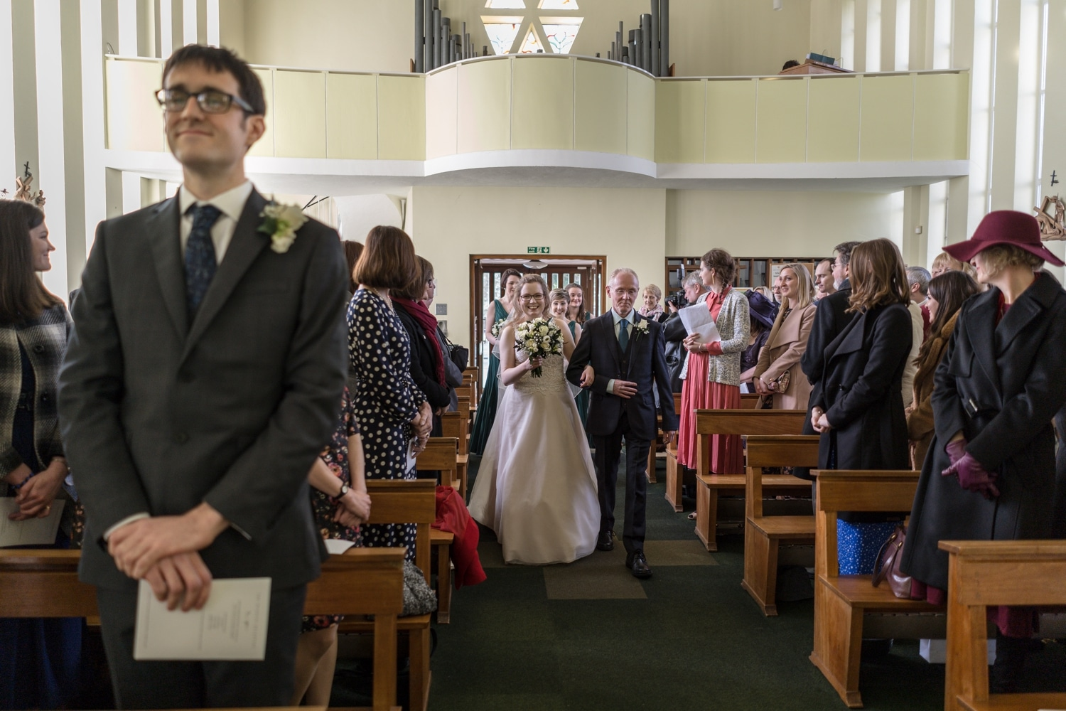Bride and father walk up aisle at St Brigid's Church, Cardiff