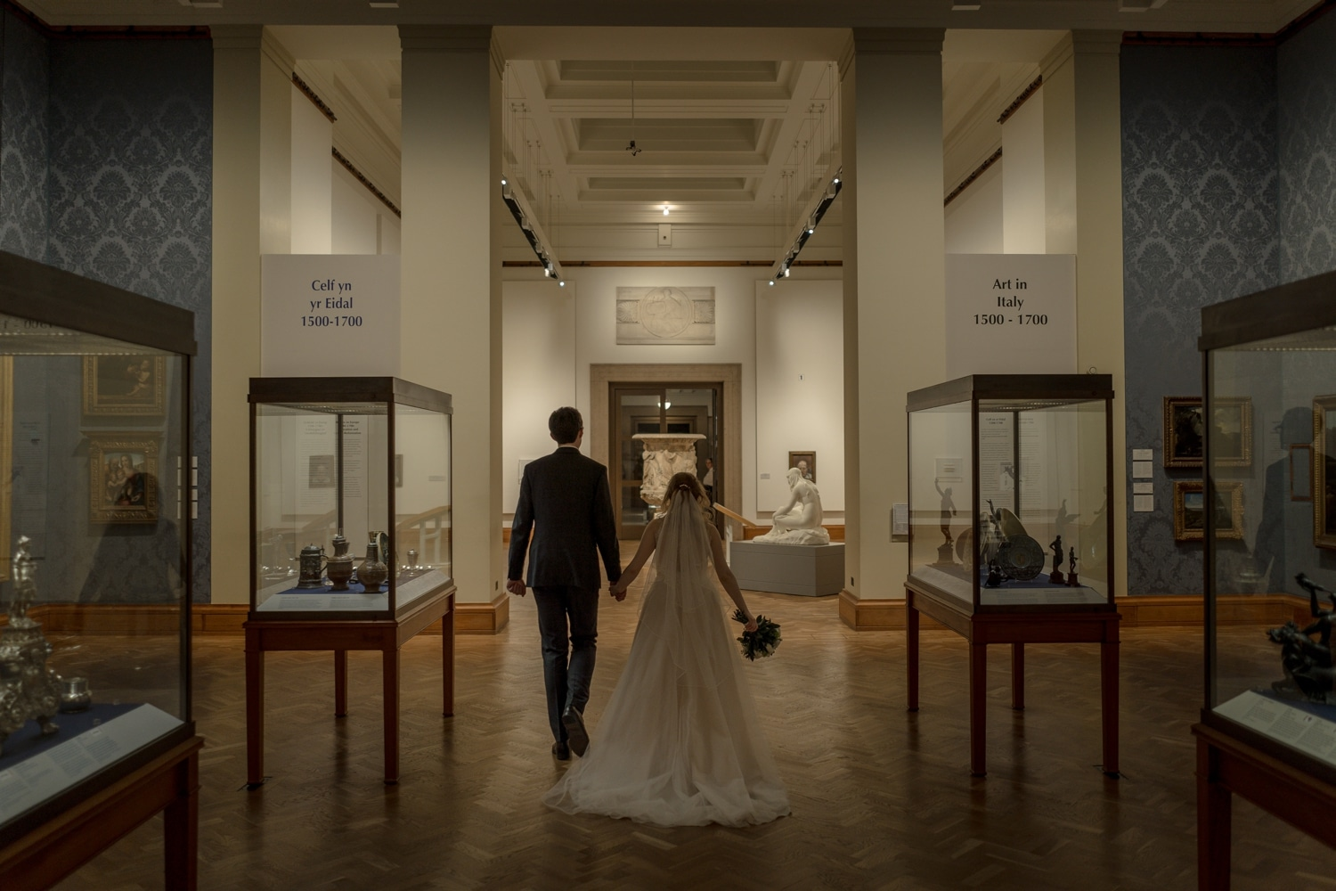 Bride and groom at Bride and groom walk though Cardiff Museum during their wedding reception