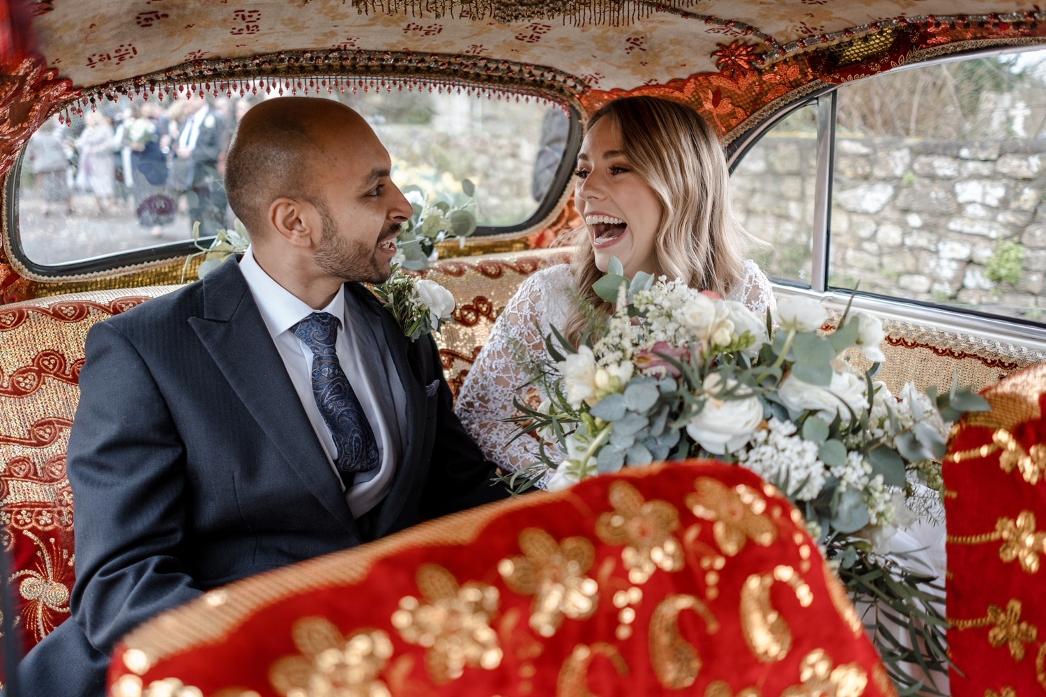 Bride laughs in wedding car which is a Indian taxi