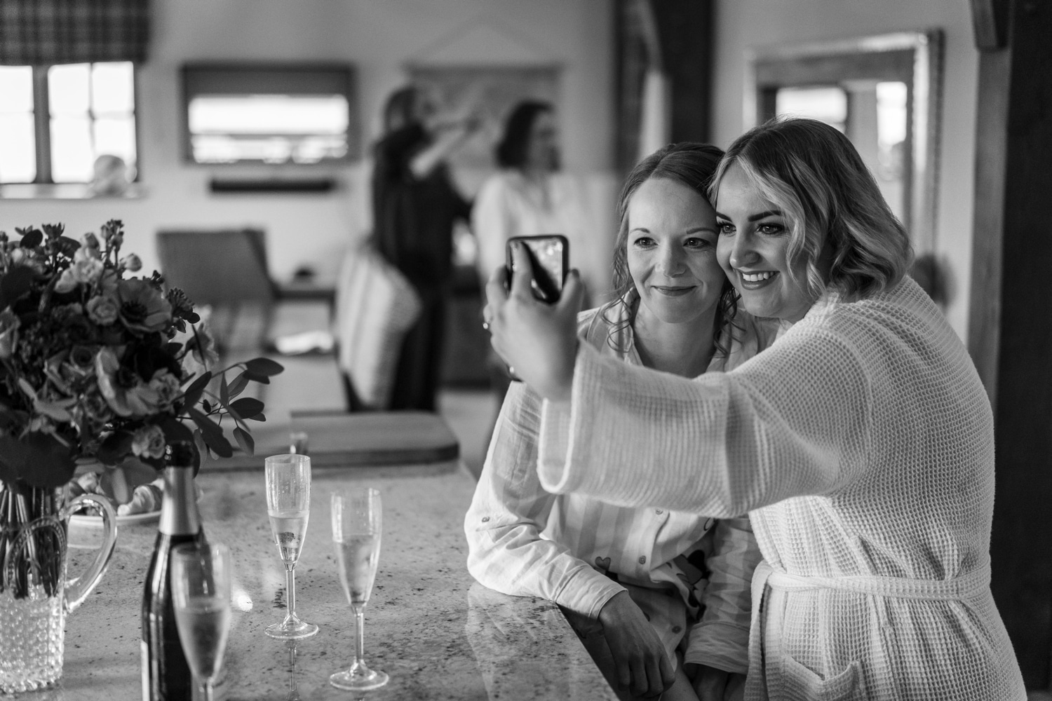 Bride and maid in gowns posing for selfie