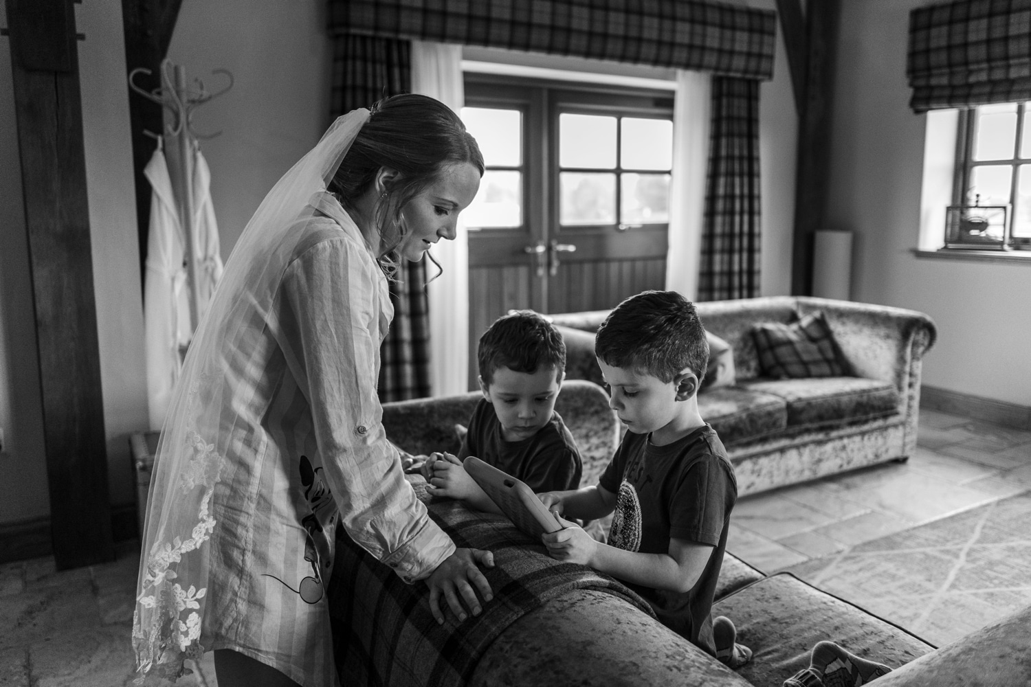 Bride with veil and pyjamas with boys playing on ipad