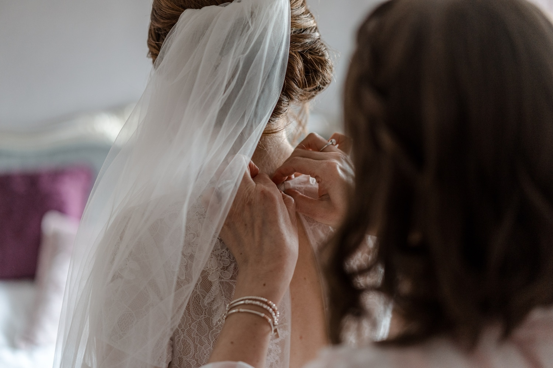 hands buttoning up brides dress
