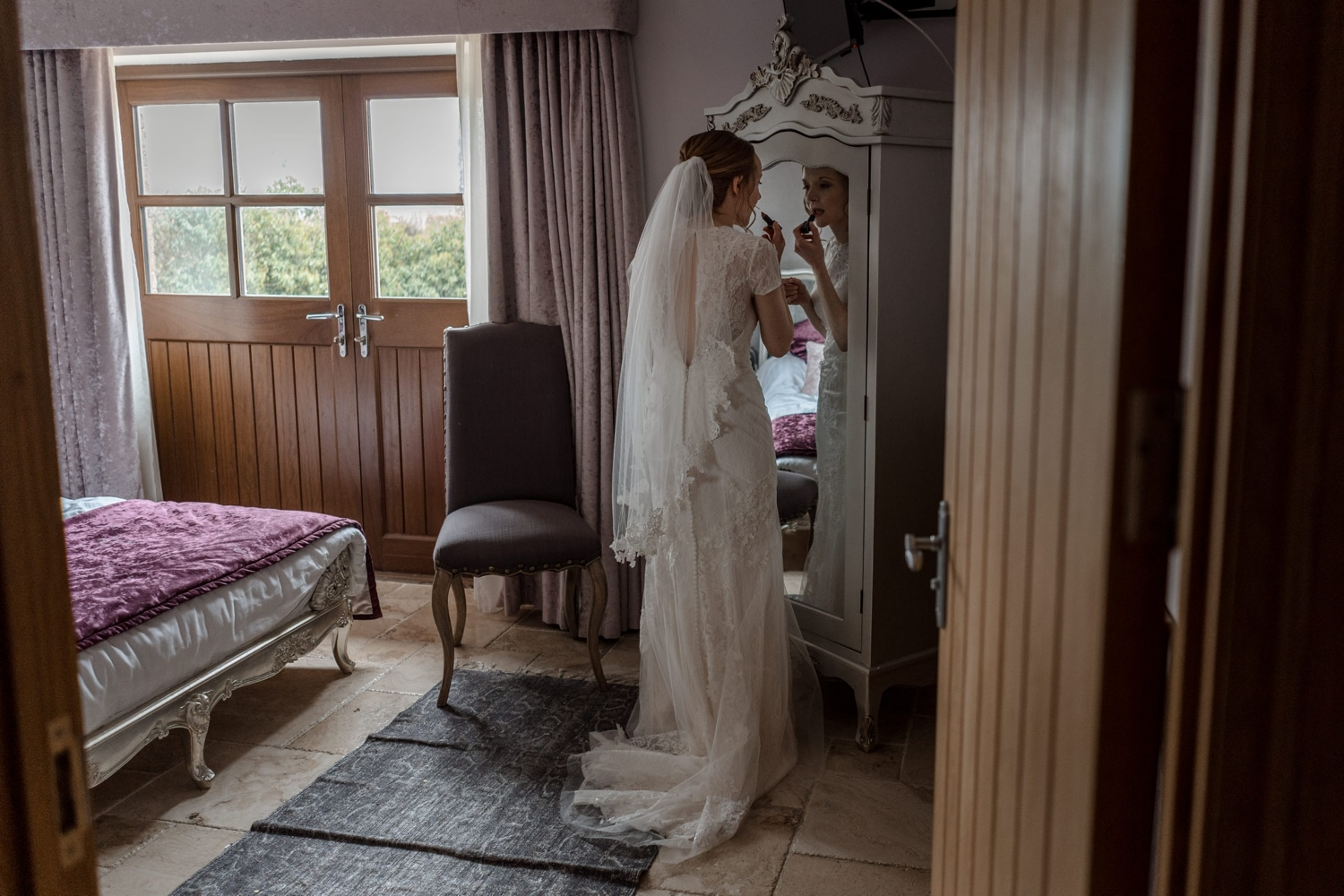 Bride putting lipstick on in front of mirror