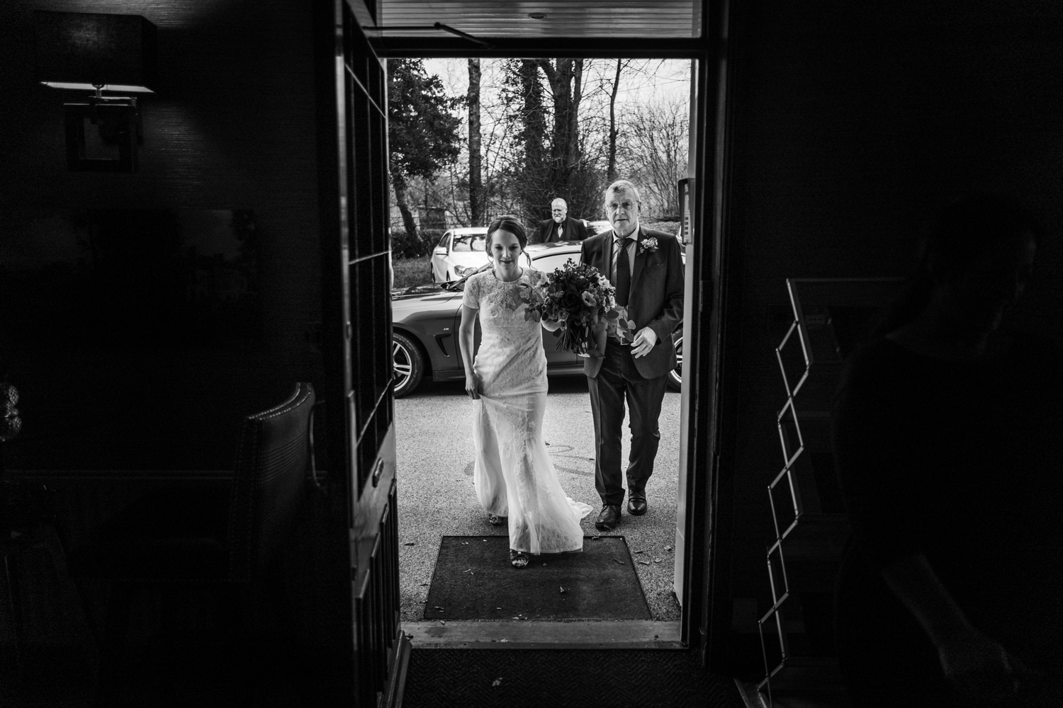 Bride walking through door with father for wedding at Fairyhill