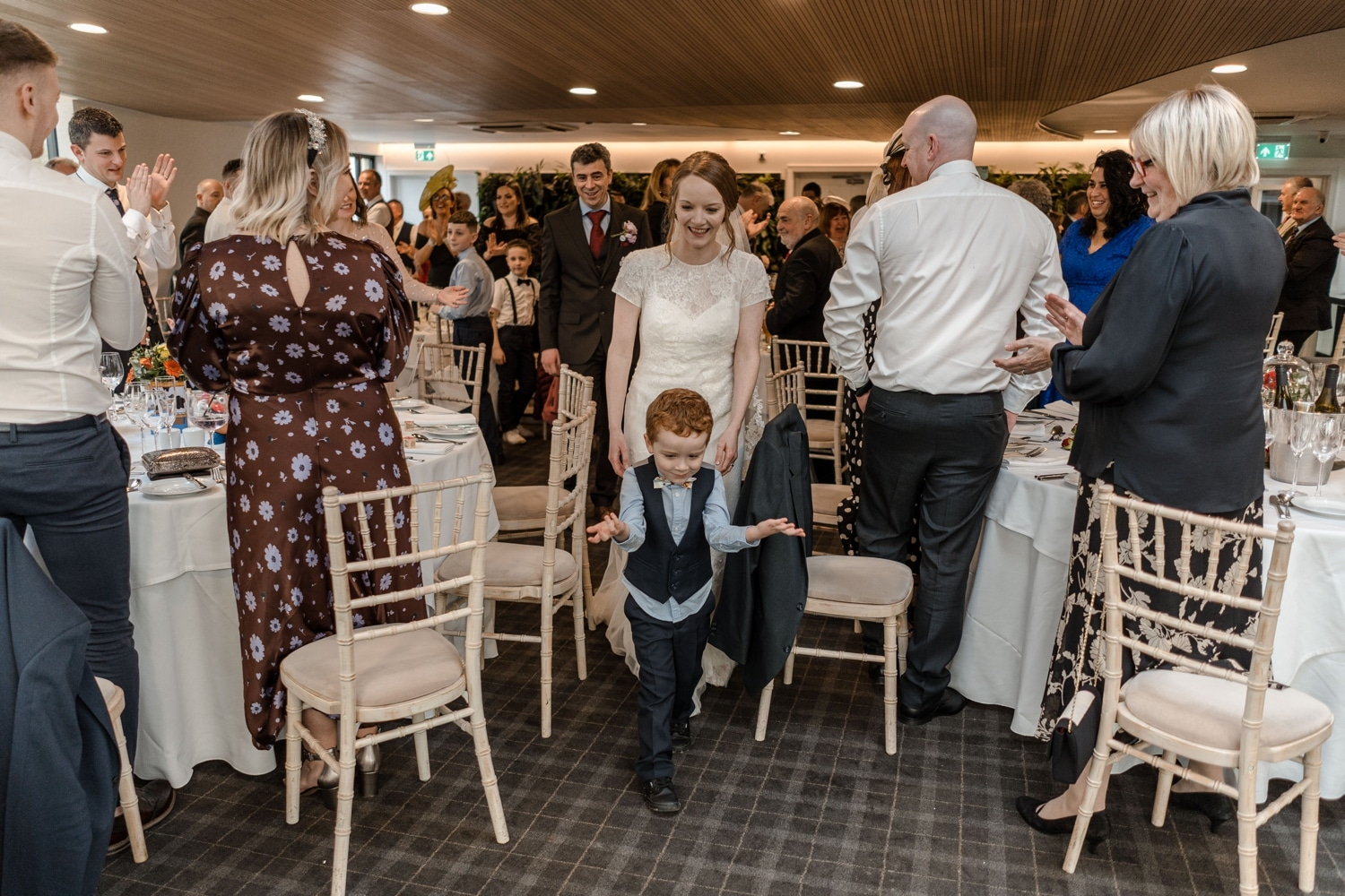 little boy leads bride and groom entrance to wedding breakfast
