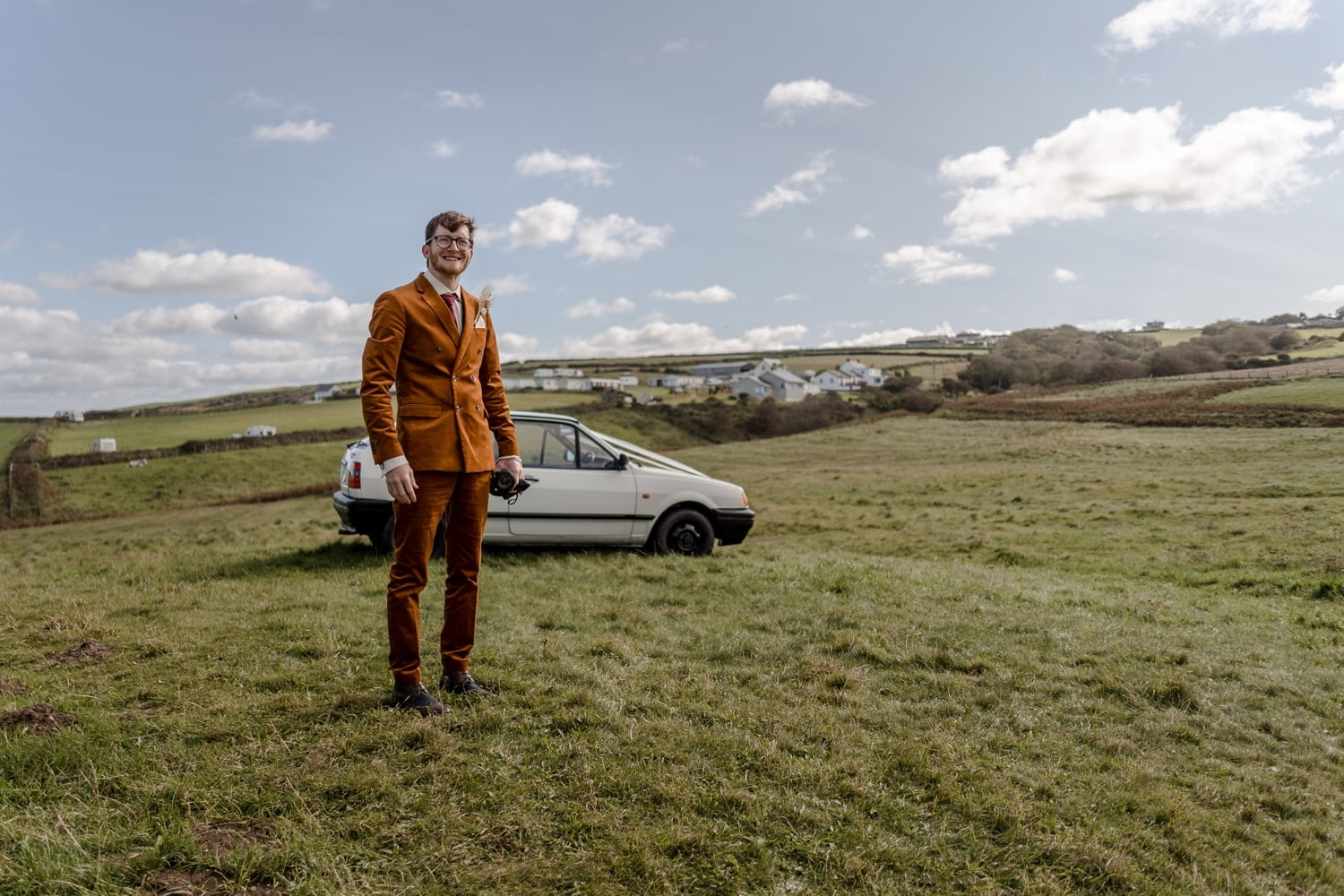 Groom with humble wedding car at Mwnt, West Wales
