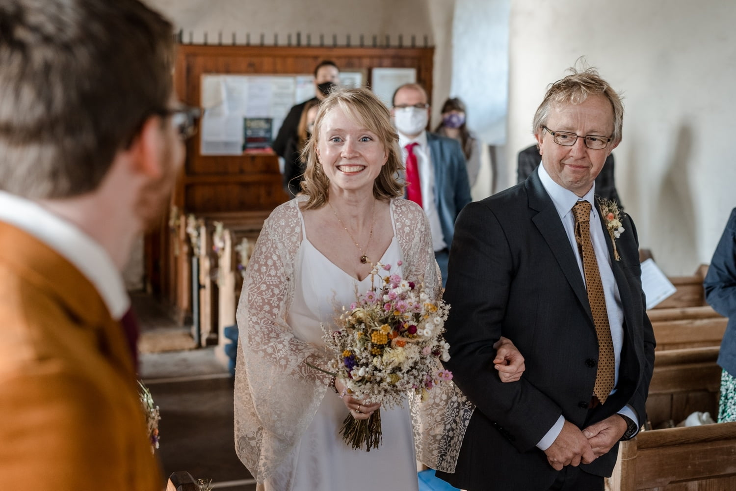 Bride walks down aisle with father at Mwnt Church