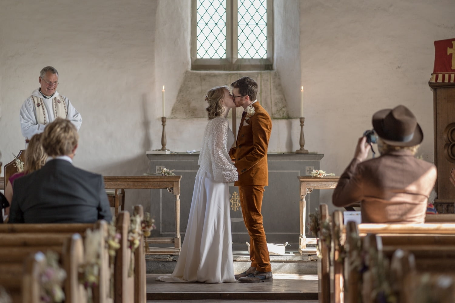 Bride and groom kissing during wedding ceremony at Mwnt Church, West Wales