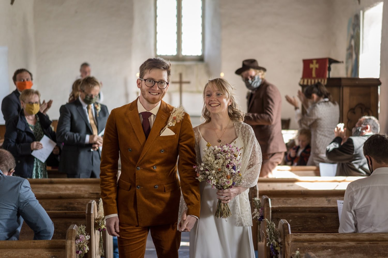 Bride and groom walking down aisle at Mwnt Church