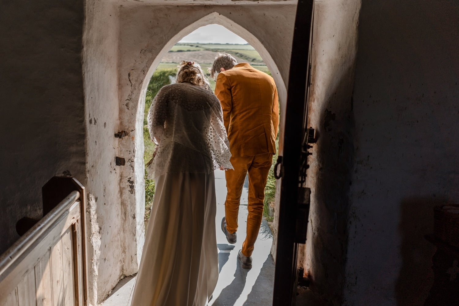 Bride and groom pass through door at Mwnt Church