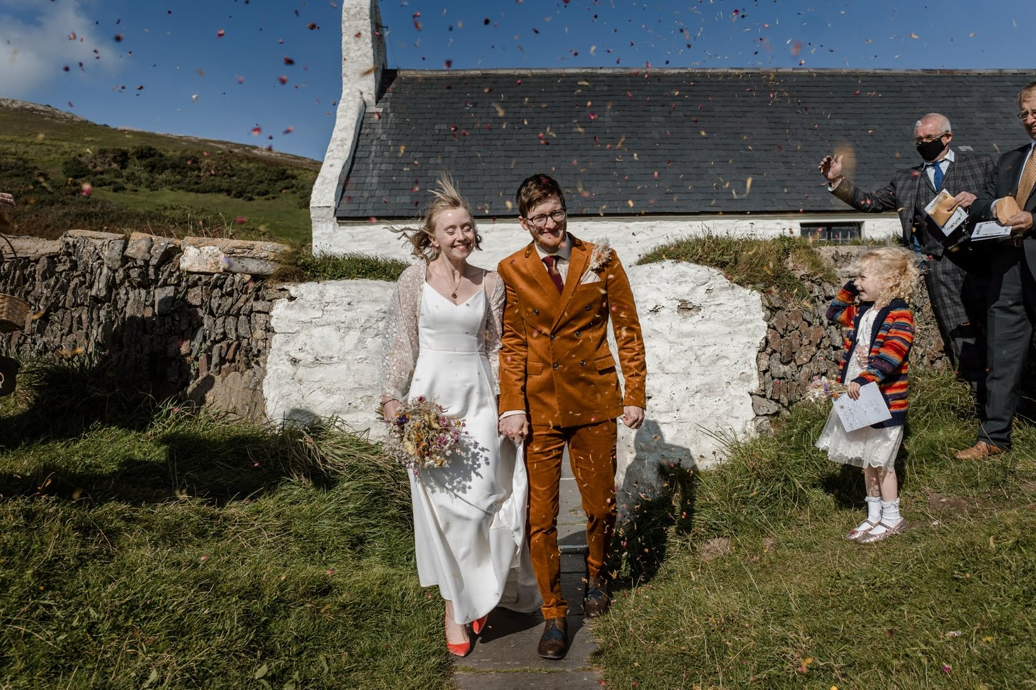 Bride and groom with confetti at Mwnt Church