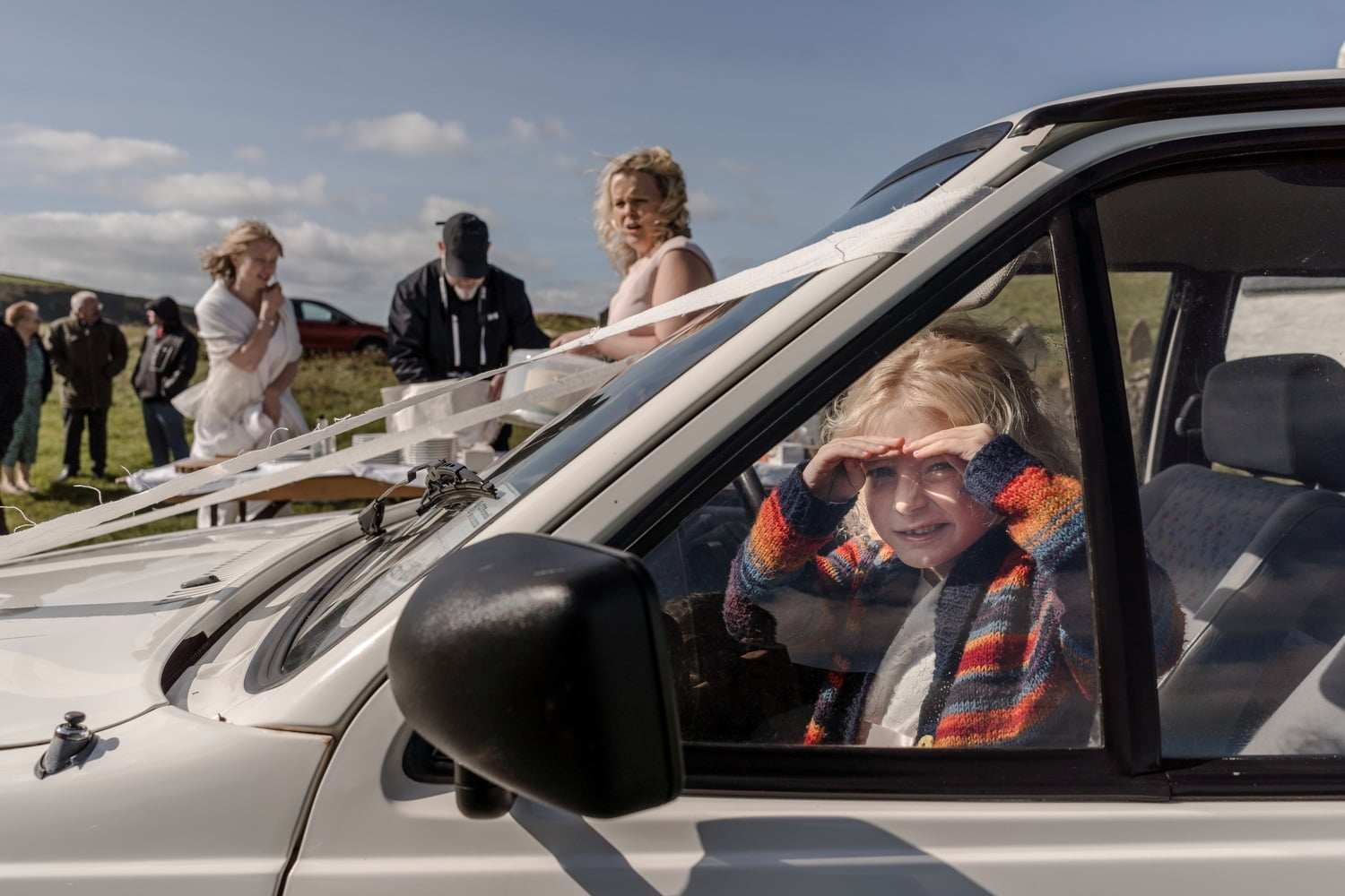 Little girl shelters in car from windy wedding reception at Mwnt Church
