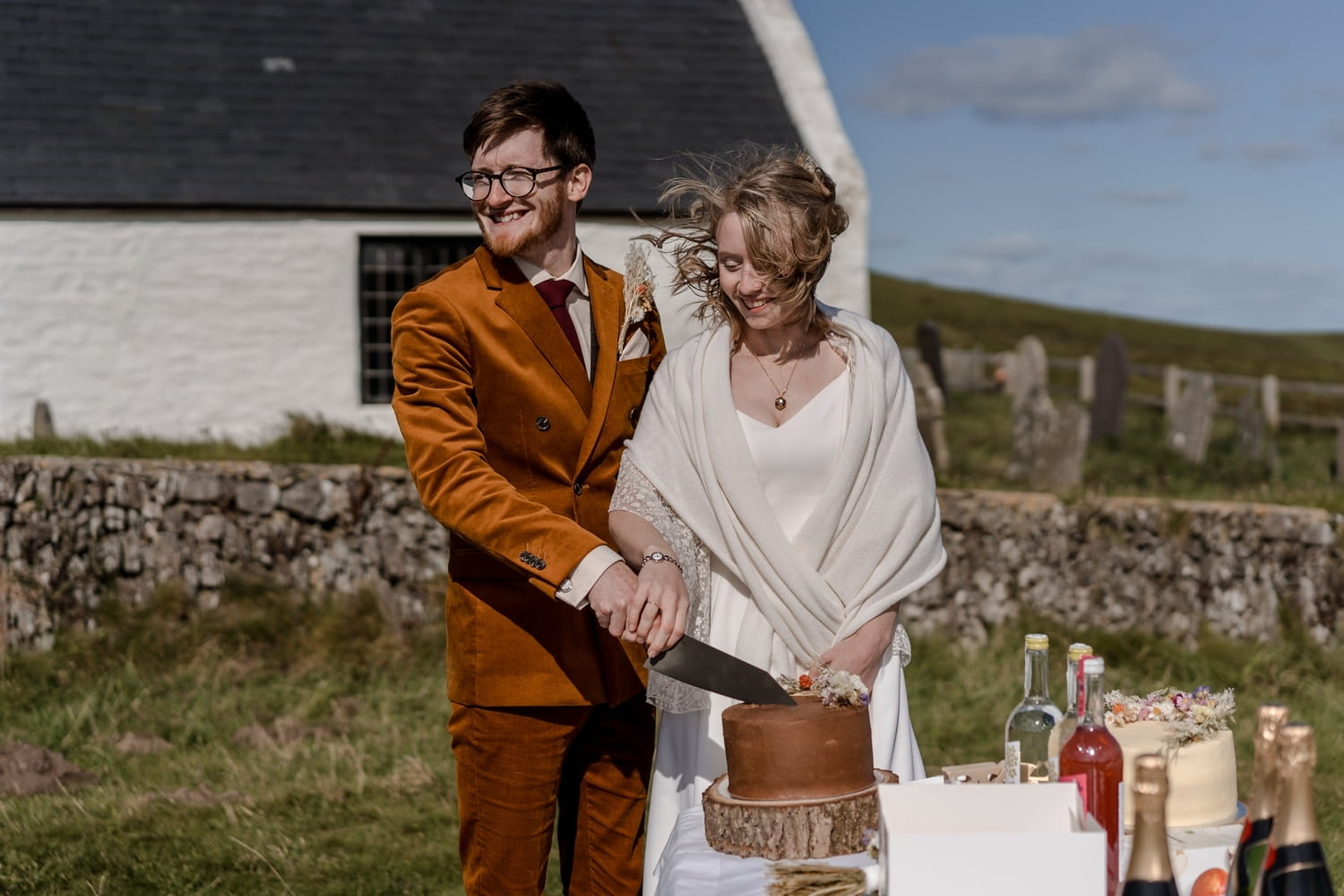 Bride and groom cut cake outside Mwnt Church