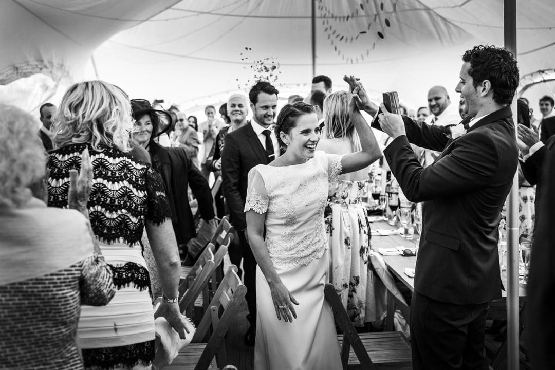 Bride high five as she walks into marquee - how to plan the perfect wedding day