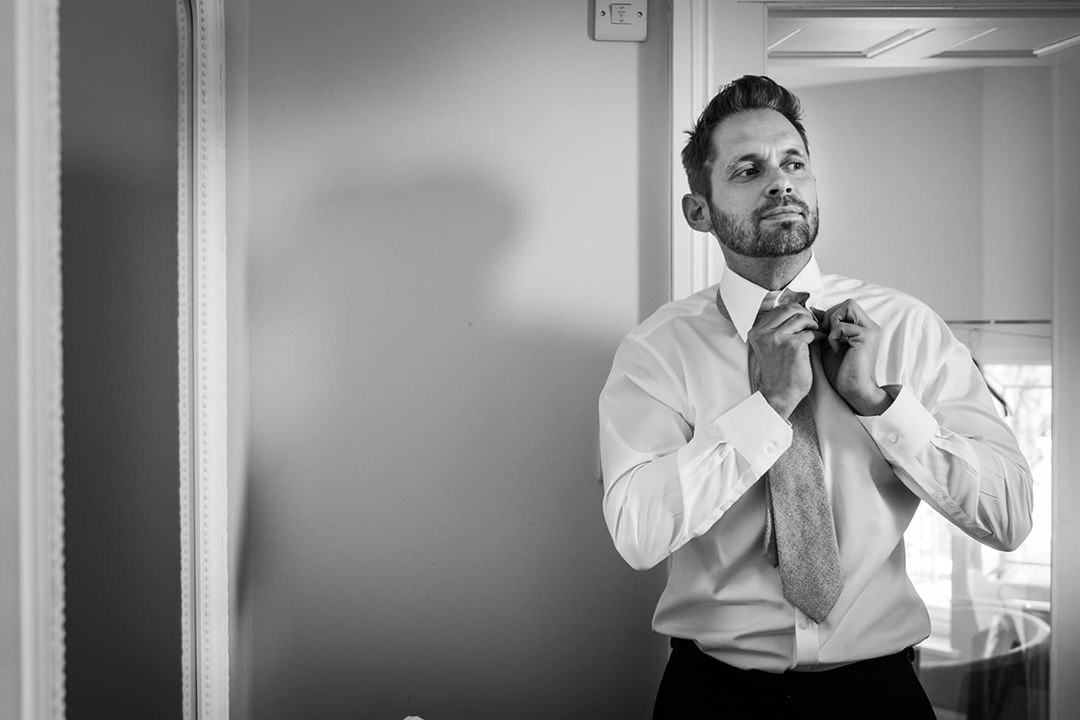 Groom getting ready buttoning shirt for wedding planning guide