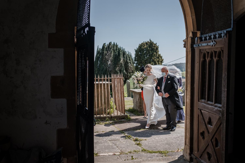 Bride with father walking through church door