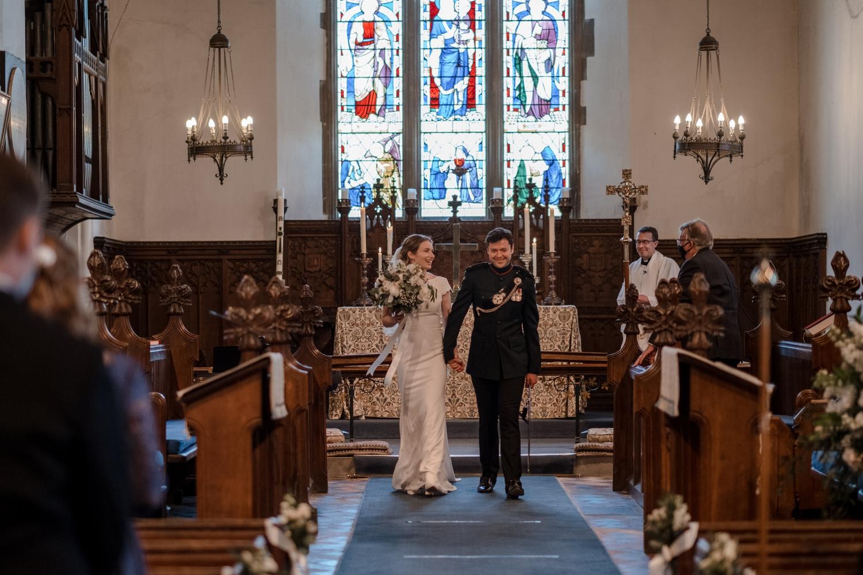 Bride and groom walk down church aisle at micro wedding