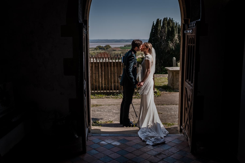 Bride and groom kiss under church doorway at micro wedding