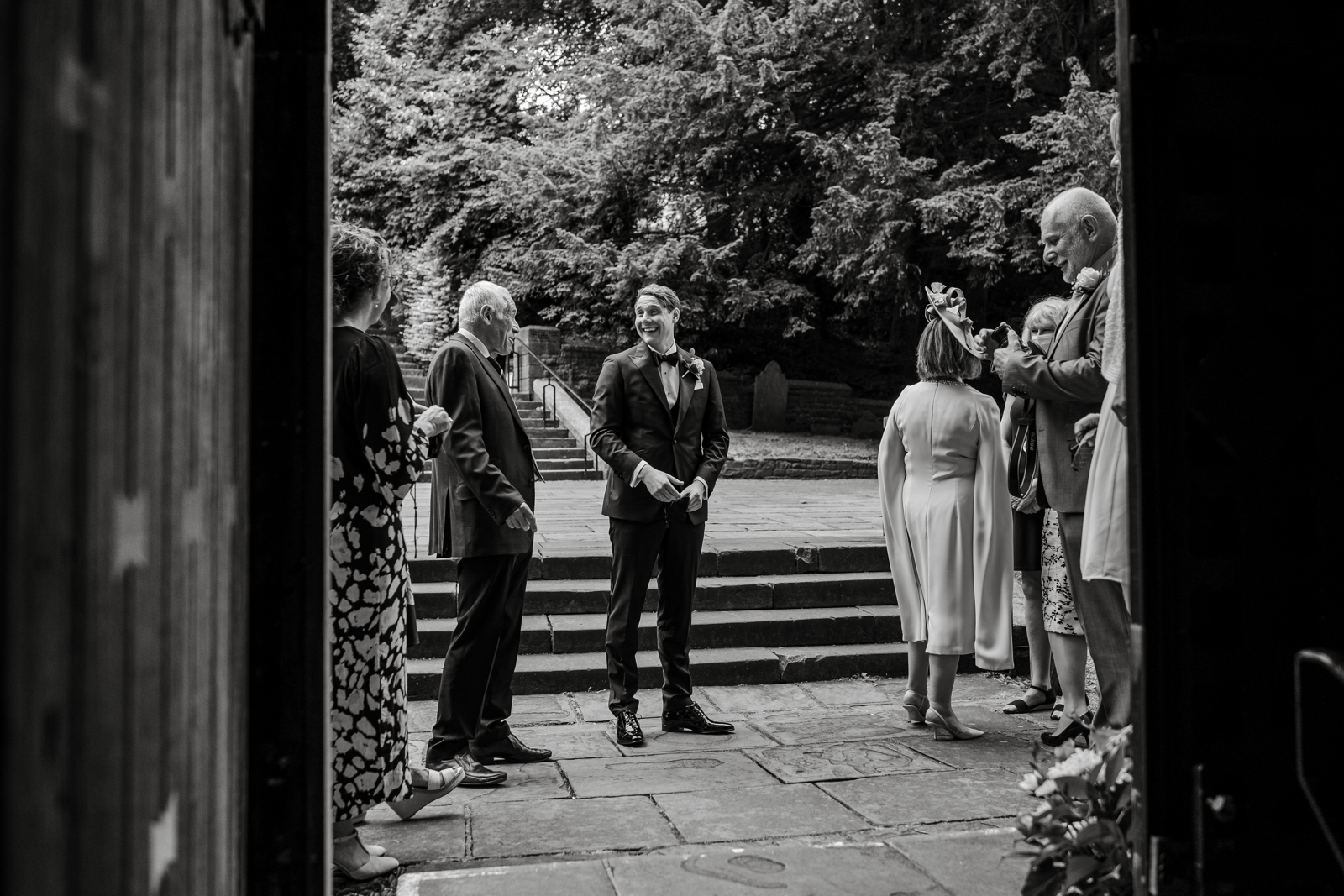 Groom chatting with guests outside Llandaff Cathedral