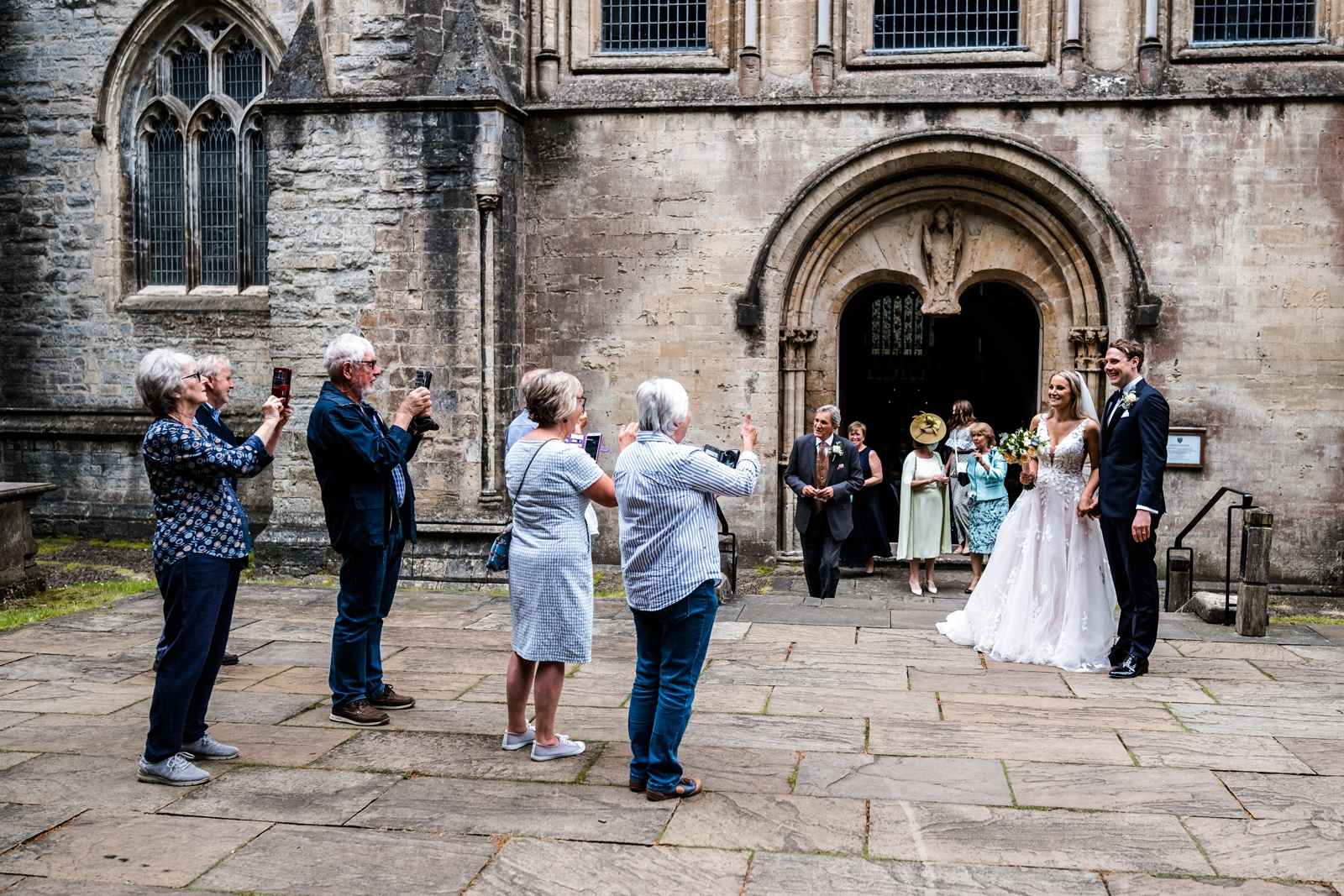 Guests outside Llandaff Cathedral taking photographs of bride and groom
