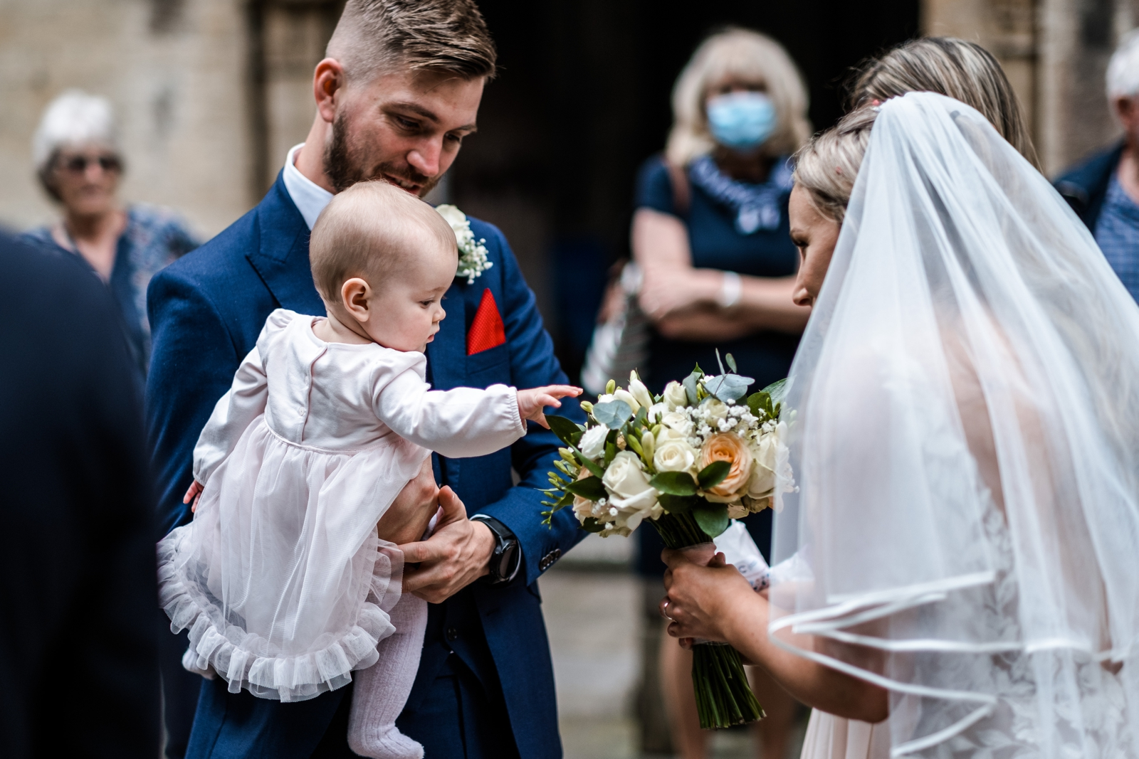 Baby reaches for bride's flowers