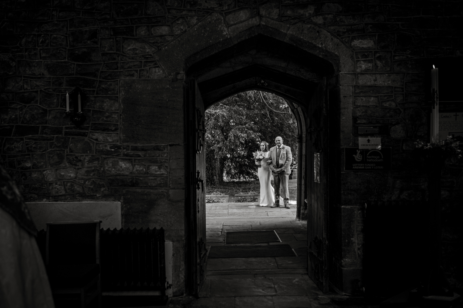 Bride and father outside Church of St Cadoc, Raglan, Monmouthshire, South Wales