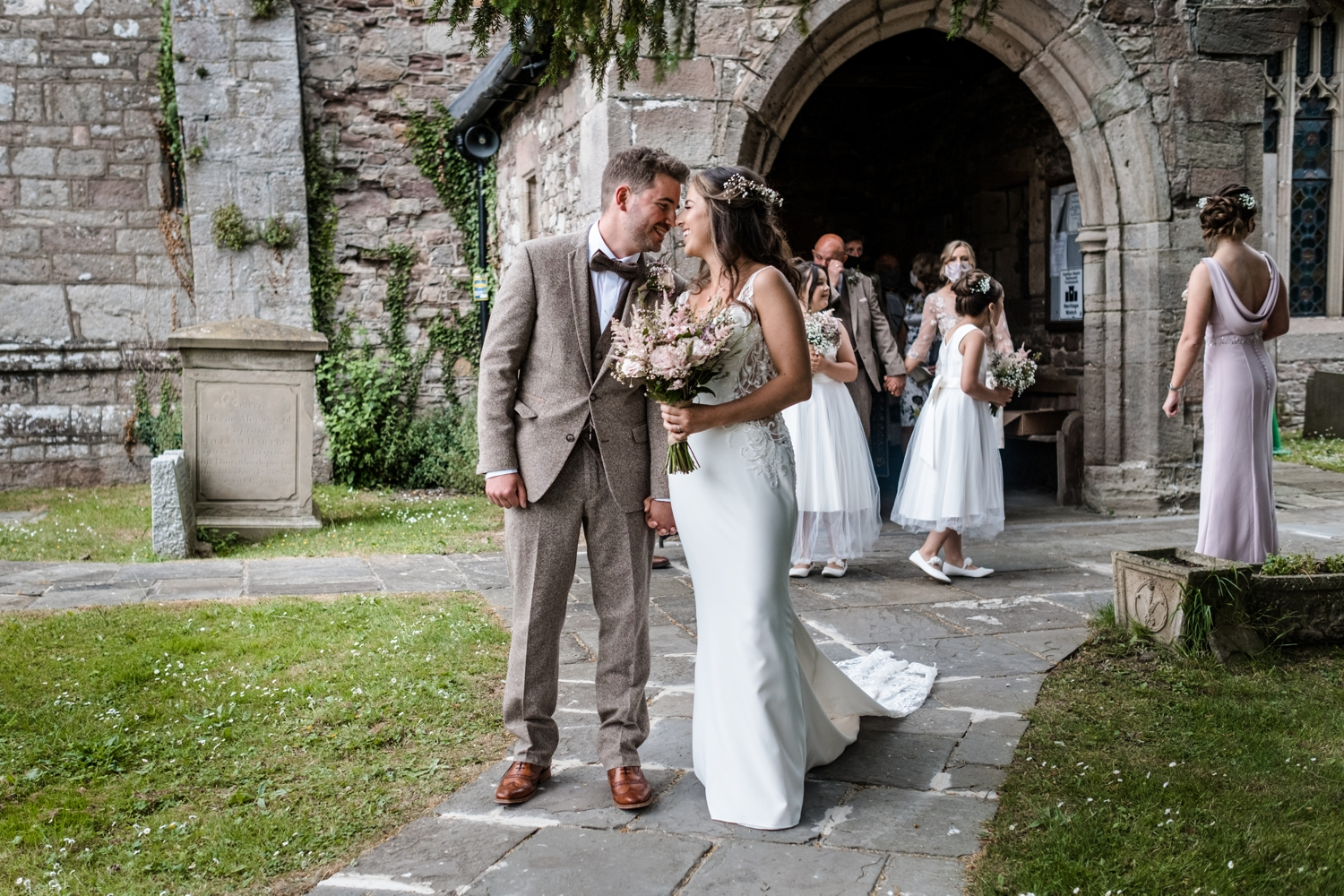Bride and groom kiss at Church of St Cadoc, Raglan, Monmouthshire, South Wales