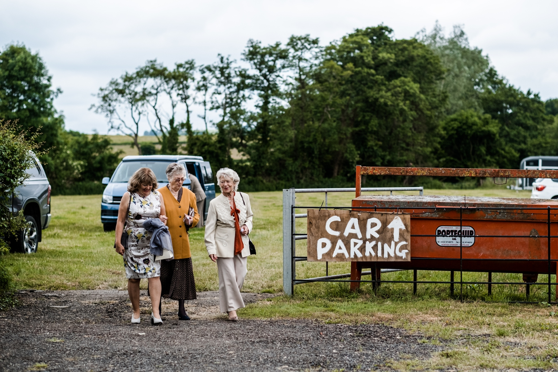 Guest park in field for Welsh farm wedding